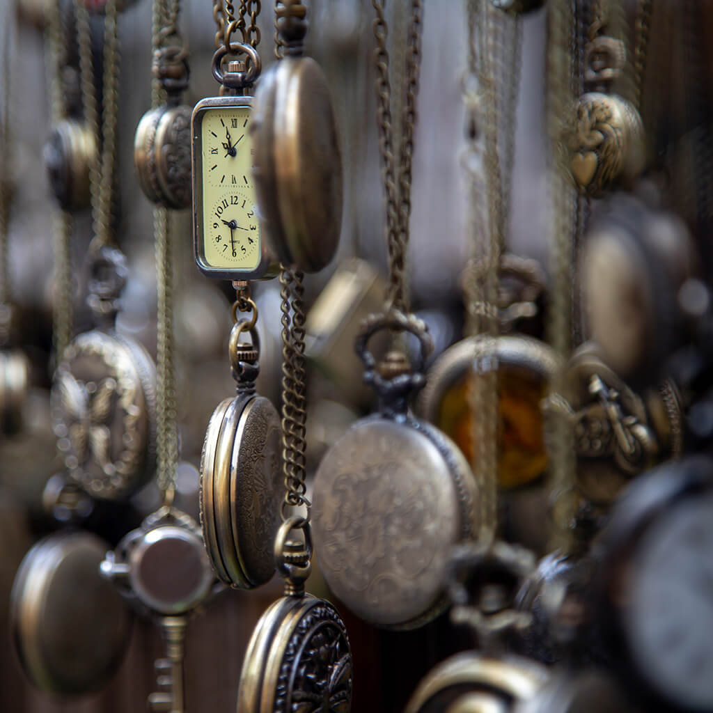 Antique pocket watches hanging in a display.